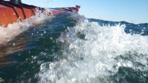 plywood kayak busting through a wave