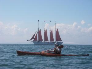 Plywood Kayak paddling near a Schooner