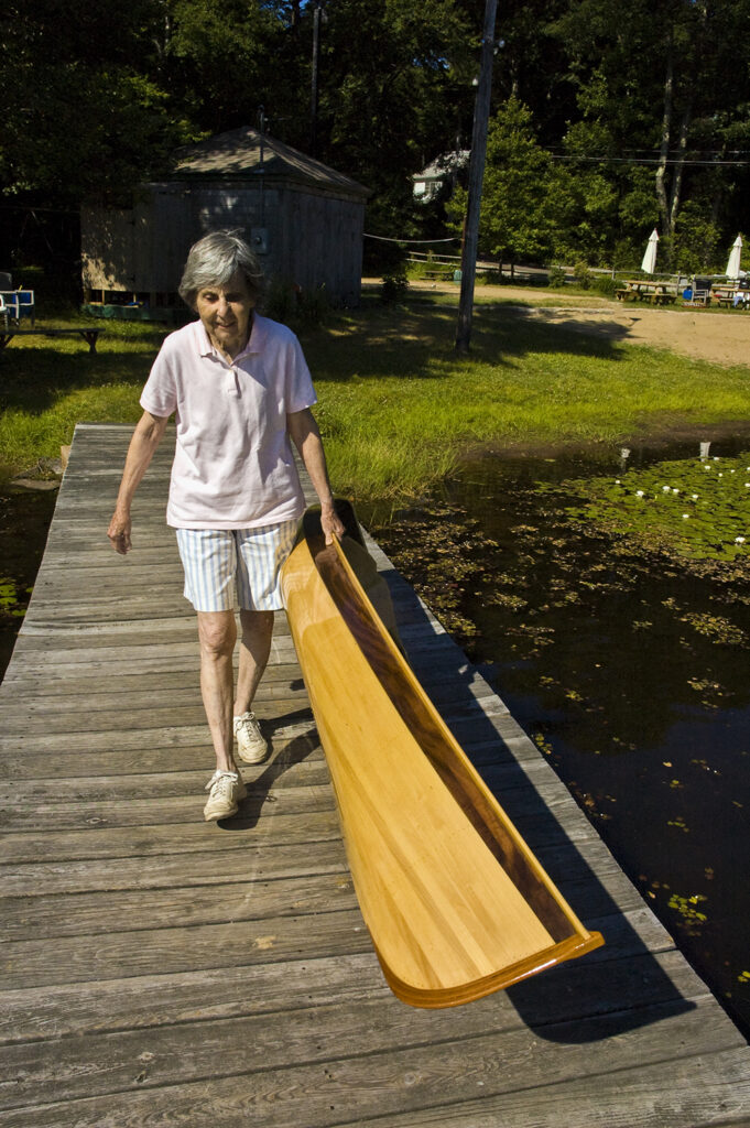 Old Woman Carrying Light Weight Wood Canoe