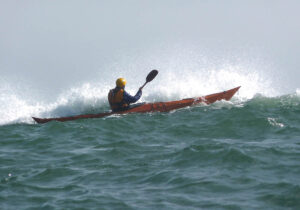Plywood Kayak paddling near a Wave