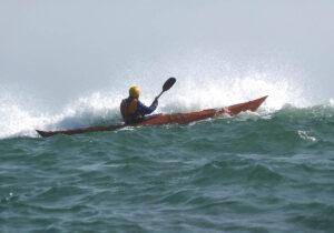 Plywood Kayak paddling near a Wave